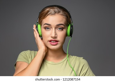 Beautiful young woman listening to music on grey background
