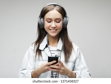 Beautiful young woman listening to music in headphones with smartphone