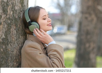 Beautiful young woman listening to music in park