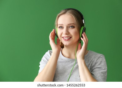Beautiful young woman listening to music against color background