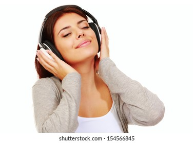 Beautiful young woman listening music in headphones isolated on white