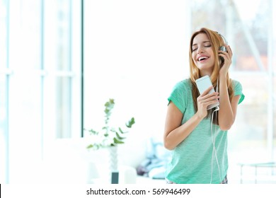 Beautiful young woman listening to music in headphones at home
