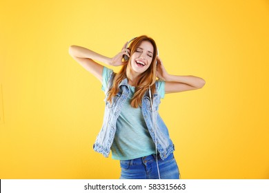 Beautiful young woman listening to music in headphones on color background