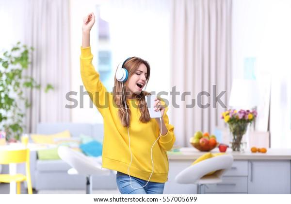 Hermosa joven mujer escuchando música con auriculares en casa