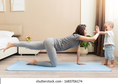 Beautiful young woman and little kid boy smiling while lying on yoga mat and doing fitness exercises at home