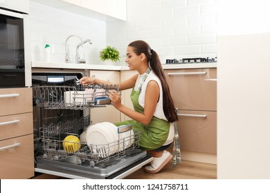 Beautiful young woman loading dishwasher in kitchen. Cleaning chores
