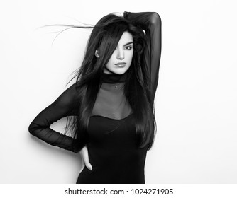 beautiful young woman with long black hair posing on grey background