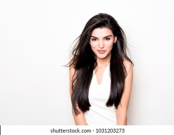 beautiful young woman with long black hair posing on white background