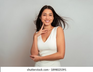 Beautiful young woman with long black hair posing in dress on grey background