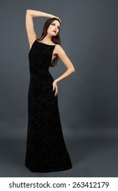 Beautiful young woman in long black dress on dark gray background