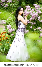 Beautiful young woman with long black hair in blooming garden