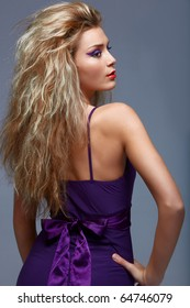 beautiful young woman with long blond hair wearing a purple evening dress.