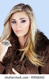 beautiful young woman with long blond hair wearing a suede fur coat on studio background