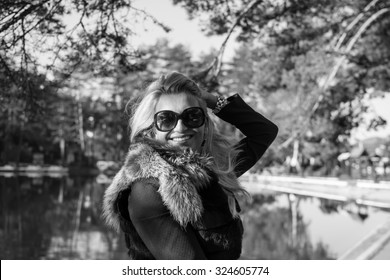 Beautiful young woman with long blonde hair, smiling. Wearing black glasses. Nature background.Black and white photo.
