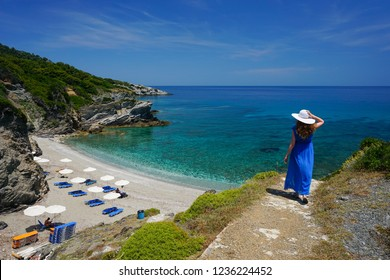 Beautiful young woman in a long blue dress, with white hat on, posing with one hand on her head on her way to Perivoliou beach. Exotic vacation on Skopelos Island in Greece