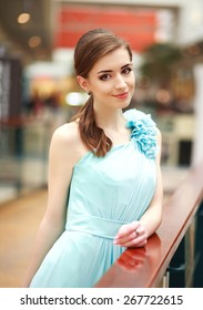 Beautiful young woman in a long blue dress, in interior