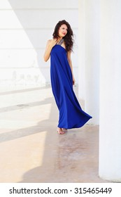 Beautiful young woman in long blue dress posing near white columns. Beautiful lady with dark hair in elegant dress posing outdoors in the summer.