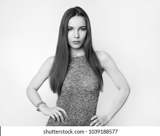 beautiful young woman with long brown hair posing on grey background in knitted dress