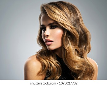 Beautiful young woman with long brown hair. Closeup portrait with a pretty female face. Fashion model with plump lips  posing at studio.