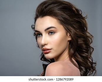 Beautiful young woman with a long brown hair. Closeup Portrait of a fashion model posing at studio