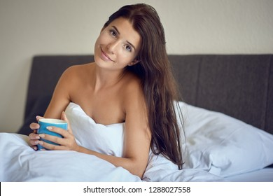 Beautiful young woman with long brown hair sitting in bed in the morning wrapped in white blanket with bare shoulders and holding blue coffee mug.