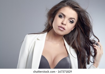 Beautiful young woman with long brown hair. Pretty model poses at studio.