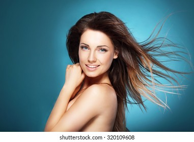 Beautiful young woman with long brown flying hair on  blue backg