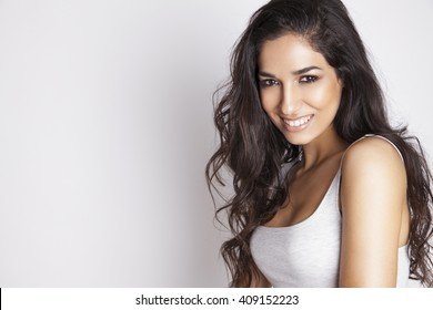 Beautiful young woman with long brown hair and white smile. Healthcare and beauty style.  Bright make up and long shiny hair concept. Studio shoot, Horizontal.