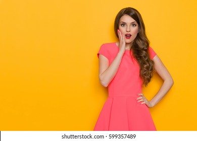 fcfe1d1ce6831 Beautiful young woman with long brown hair posing in pink mini dress  holding hand on chin