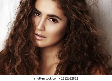 Beautiful young woman with long curly hairstyle, fashion jewelry with long brunette hair. Sexy girl in vogue style. Pretty arabian beauty portrait of female face. Indian style clothes, long dress