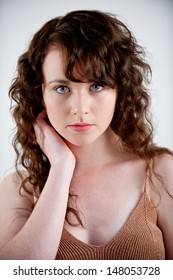 Beautiful young woman with long curly hair posing in a studio