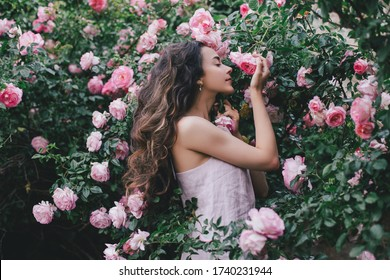 Beautiful young woman with long curly hair and perfect skin wearing pink linen dress posing near blooming roses in a garden. Nude make up. Close up portrait