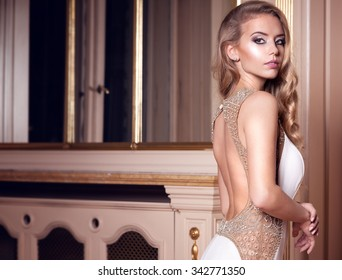 Beautiful young woman with long curly hair posing in white wedding dress in luxury palace. Attractive bride .