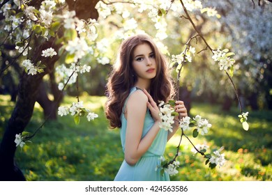 Beautiful young woman with long curly hair and blossom flowers