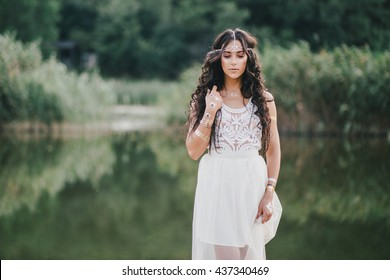 Beautiful young woman with long curly hair dressed in bohemian style dress posing near lake