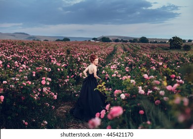 Beautiful young woman with long curly hair posing near roses in a garden. The concept of perfume advertising.