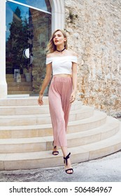Beautiful young woman with long curly blonde hair with a beautiful make-up walking from modern hotel. Around her neck is a stylish black choker and she is dressed in a pink pants and white blouse.