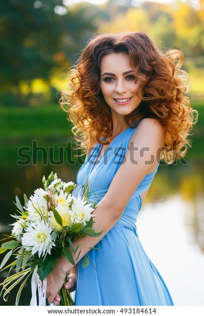 Beautiful young woman with long curly hair posing with bouquet