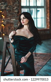 Beautiful young woman with long dark hair in sexy elegant dress with bare shoulders.  Evening fashion luxury look