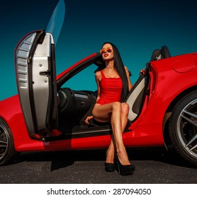 beautiful young woman with long dark hair in red bodysuit and sunglasses sitting in red cabrio