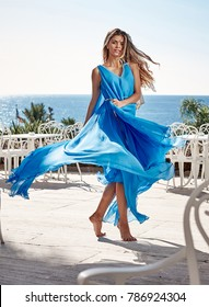 Beautiful young woman with long dark hair wearing long blue dress and dancing on stunning sea view background at summer