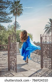 Beautiful young woman with long dark hair wearing long blue dress and running away on stunning sea view background at summer