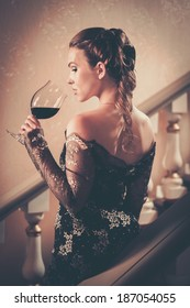 Beautiful young woman in long evening dress with glass of red wine standing on a steps in luxury interior