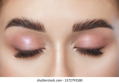 Beautiful young woman with long eyelashes, beautiful fresh nude make-up, thick eyebrows and with clean skin in a beauty salon. Eyelash extensions. Eyebrows close up. Makeup and Cosmetology concept.