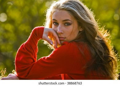 Beautiful young woman with long golden hair in park
