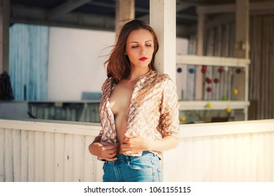 Beautiful young woman with long hair and red lips in stylish golden sparkle sequins jacket and jeans street fashion. Bare shoulders.