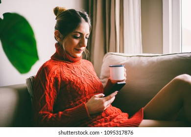 Beautiful young woman with long hair sitting and looking at smartphone screen on sofa, drinking coffee (toned image, selective focus)