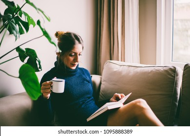 Beautiful young woman with long hair, sitting on sofa, reading a book and drinks coffee (toned image, selective focus)