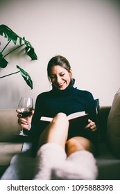 Beautiful young woman with long hair, sitting on sofa, reading a book and drinks red wine (toned image, selective focus)
