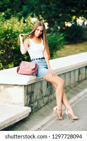 Beautiful young woman with long hair wearing white shirt and jeans skirt  walking on the street. Long woman's legs with smooth skin in high heel shoes